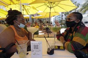 Two patrons wear facemasks at a restaurant on Miami Beach on Friday (Wilfredo Lee/AP)