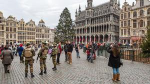Belgian soldiers patrol as tourists visit the Grand Place in Brussels (AP)