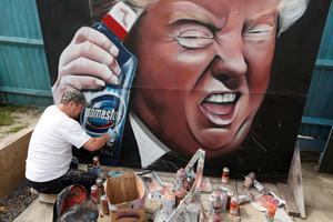 Gaffe: Dave Nash spray-paints a mural of President Donald Trump in Royston, Britain, holding a bottle of Domestos bleach, following his coronavirus treatment comments. Photo: Matthew Childs/Reuters