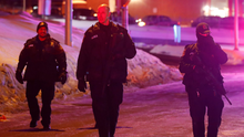 Police officers patrol the perimeter near a mosque after a shooting in Quebec City which left six people dead Photo: REUTERS/Mathieu Belanger