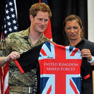 Prince Harry, standing with Misty May Treanor, is presented a t-shirt at the Warrior Games