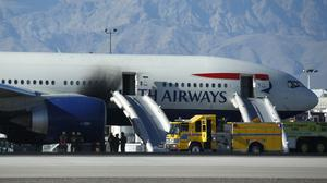 Firefighters stand by a plane that caught fire at McCarren International Airport in Las Vegas (AP)