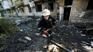 A firefighter carries a water hose at a damaged apartment building after shelling in Donetsk (AP)