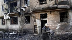 A firefighter tackles a damaged apartment building after shelling in the town of Donetsk (AP)