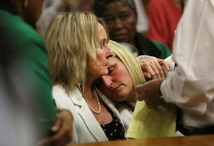 Mother and cousin of the late Reeva Steenkamp, June Steenkamp, left, and Kim Martin, right, comfort one another in court in Pretoria. Photo: AP