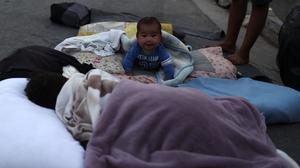 A baby crawls as migrants remain camped out on a road in Lesbos (Petros Giannakouris/AP)