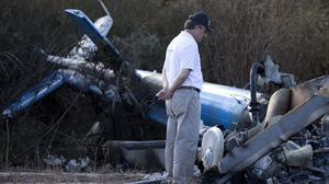 A civil aviation accident investigator inspects the wreckage of one of two helicopters that collided in mid-air, near Villa Castelli in Argentina (AP)