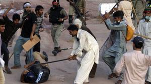 Pakistani protesters beat a police officer during a clash in Islamabad. (AP)