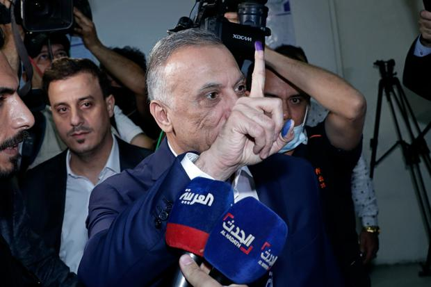 Iraqi Prime Minister Mustafa al-Kadhimi, centre, show his ink-stained finger after voting in the parliamentary elections (Khalid Mohammed/AP)