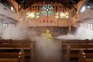 Precaution: A worker disinfects the Hankou Salvation Church in Wuhan, in China's central Hubei province, yesterday. Photo: STR/AFP via Getty Images
