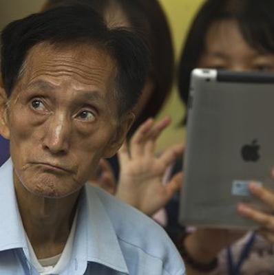 An elderly man watches tutorial videos after he bought a new iPad at an Apple Store in Beijing (AP)