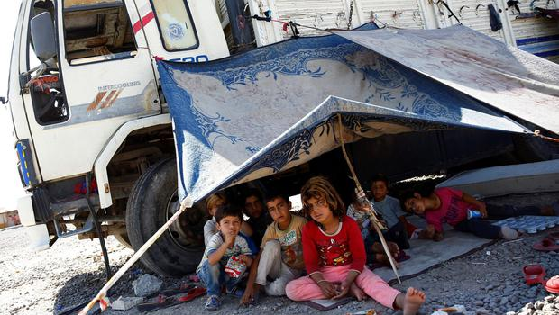 Refugee children from the northern Syrian town of Tel Abyad sit under a makeshift tent in Akcakale, Turkey