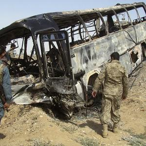 Afghan police and army soldiers inspect the burned-out bus (AP)