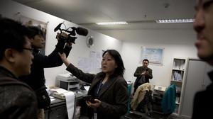 A staff member at the Malaysian Airlines' office in Beijing's International Airport reacts to journalists in Beijing (AP)