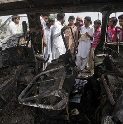 Pakistanis gather by the wreckage of a school minibus, which caught fire killing 17 in Gujrat (AP)