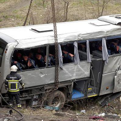 A crane lifts a bus which crashed in Belgium, leaving at least five people dead (AP)