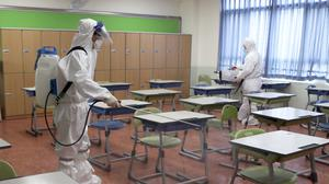 Workers wearing protective gear disinfect as a precaution against the new coronavirus in a class at a high school in Busan, South Korea (Jo Jung-ho/AP)