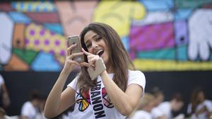 Miss Lebanon, Saly Greige, poses for photos after she painted on a wall in Miami's Wynwood area (AP)