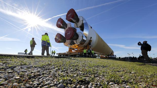 Security and safety personnel walk with the core stage of Nasa's Space Launch System rocket (Gerald Herbert/AP)