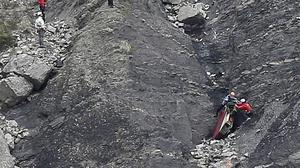 Rescue workers deal with debris at the plane crash site near Seyne-les-Alpes, France (AP)