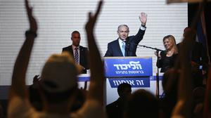 Israeli Prime Minister Benjamin Netanyahu greets supporters at the party's election headquarters In Tel Aviv. (AP Photo/Oded Balilty)
