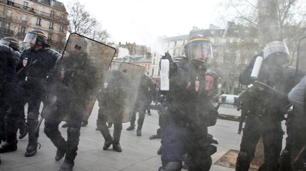 A riot police officer sprays pepper gas during a high school protest against labour reforms in Paris (AP)