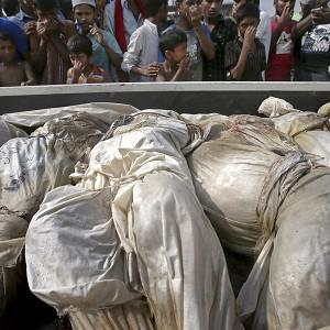 Bodies of victims are taken to the cemetery on a truck (AP)