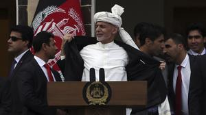 Afghan President Ashraf Ghani, centre, opens his coat after a few rockets are fired during his speech after being sworn, at his inauguration ceremony at the presidential palace in Kabul, Afghanistan (Rahmat Gul/AP)
