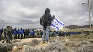 A settler holds an Israeli flag outside the West Bank outpost of Amona (AP)