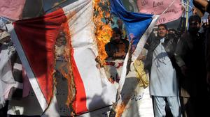 Demonstrators in Peshawar, Pakistan, burn a representation of a French flag during a protest against Charlie Hebdo cartoons (AP)