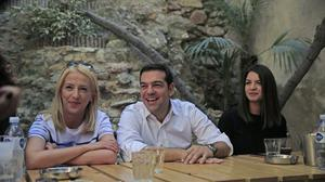 Syriza left-wing party leader and former prime minister Alexis Tsipras, centre, laughs as he meets with young people at a coffee shop (AP)
