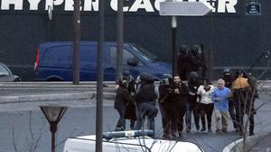 Security officers escort released hostages after they stormed a kosher market to end a hostage situation, in Paris (AP)
