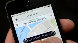 The Uber app being used on a smartphone, as two executives face trial in France over the company's banned low-cost service