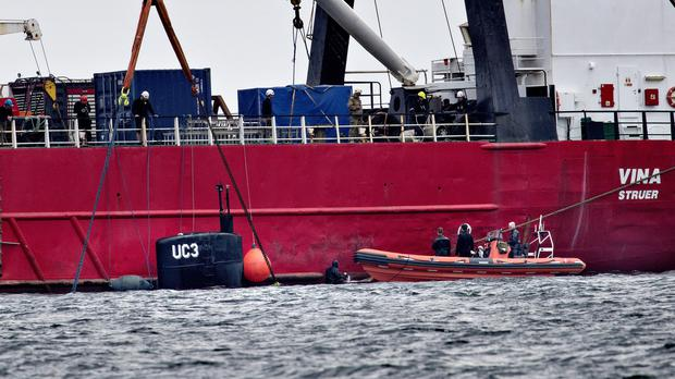 The privately built and owned submarine is brought to the surface by a salvage vessel