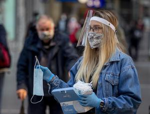 A woman working for the regional public transport company offers face masks in the main train station in Frankfurt (Michael Probst/AP)