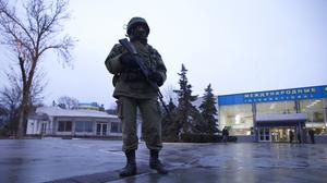 An unidentified armed man patrols a square in front of the airport in Simferopol, Ukraine