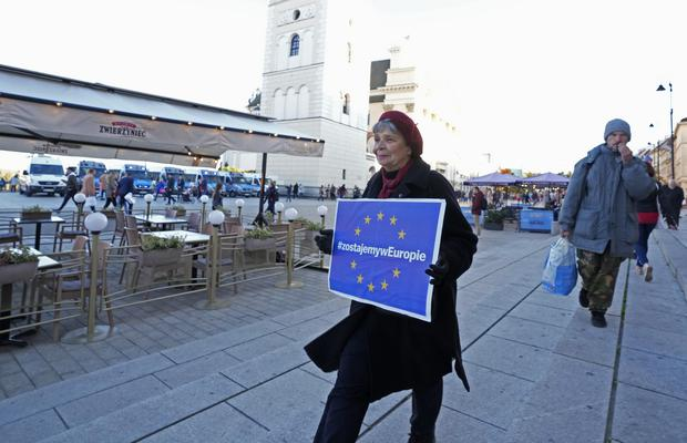 A protester in Warsaw holds a sign in support of Poland's EU membership (Czarek Sokolowski/AP)