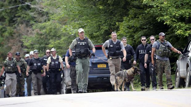 Law enforcement officers walk along a road as the search continues for two escaped prisoners from the Clinton Correctional Facility in Dannemora (AP)