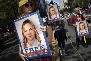 People hold signs calling for the release of imprisoned wikileaks whistleblower Chelsea Manning while marching in a gay pride parade in San Francisco,