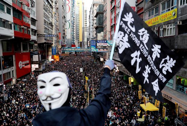 Anger on the streets: a protester wearing a Guy Fawkes mask waves a flag during a Human Rights Day march, organised by the Civil Human Right Front, in Hong Kong this week.