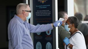 A woman has her temperature taken before entering Prairie Meadows Casino in Iowa (Charlie Neibergall/AP)