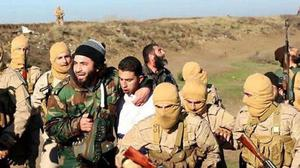 Members of the Islamic State group with a captured Jordanian pilot, centre in white (AP Photo/Raqqa Media Center of the Islamic State group)