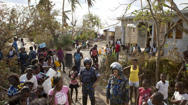 United Nations police stand with residents in Sous-Roche, outside Les Cayes (AP)