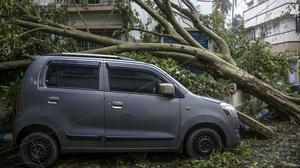 A damaged car after an uprooted tree fell on it after Cyclone Amphan hit the region in Kolkata, India (Bikas Das/AP)
