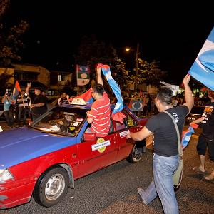 Supporters of Malaysian opposition leader Anwar Ibrahim wave flags as they drive through the streets after polls closed in Kuala Lumpur (AP)