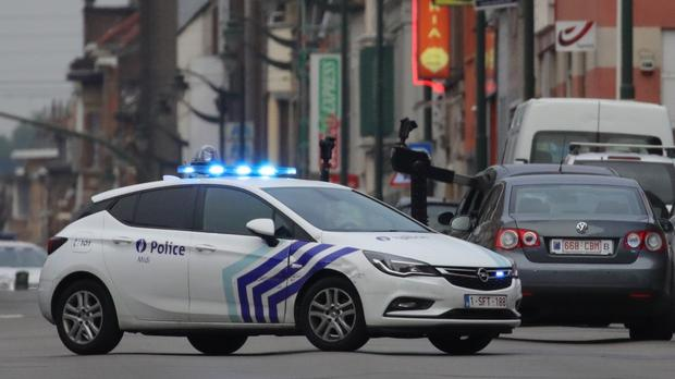 A police vehicle blocks a road in front of a bomb disposal robot in the Molenbeek suburb of Brussels (Olivier Matthys/AP)