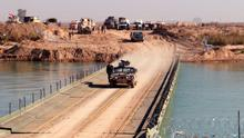 Iraqi pro-government forces cross a bridge over the Euphrates river near Ramadi. Photo: Getty Images