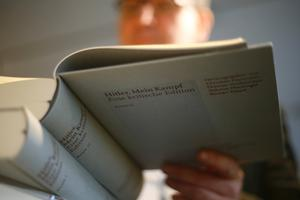 The owner of a book shop looks through a copy of the book  'Hitler, Mein Kampf. A Critical Edition' in Munich, Germany.  Photo: Reuters/Michael Dalder