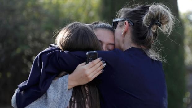 People embrace near the Tocqueville secondary school after a shooting incident injuring at least eight people, in Grasse, southern France, yesterday.