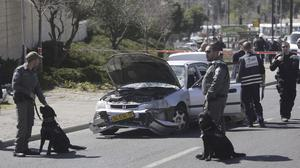 Israeli police stand next to a car at the scene of an apparent attack in Jerusalem (AP)